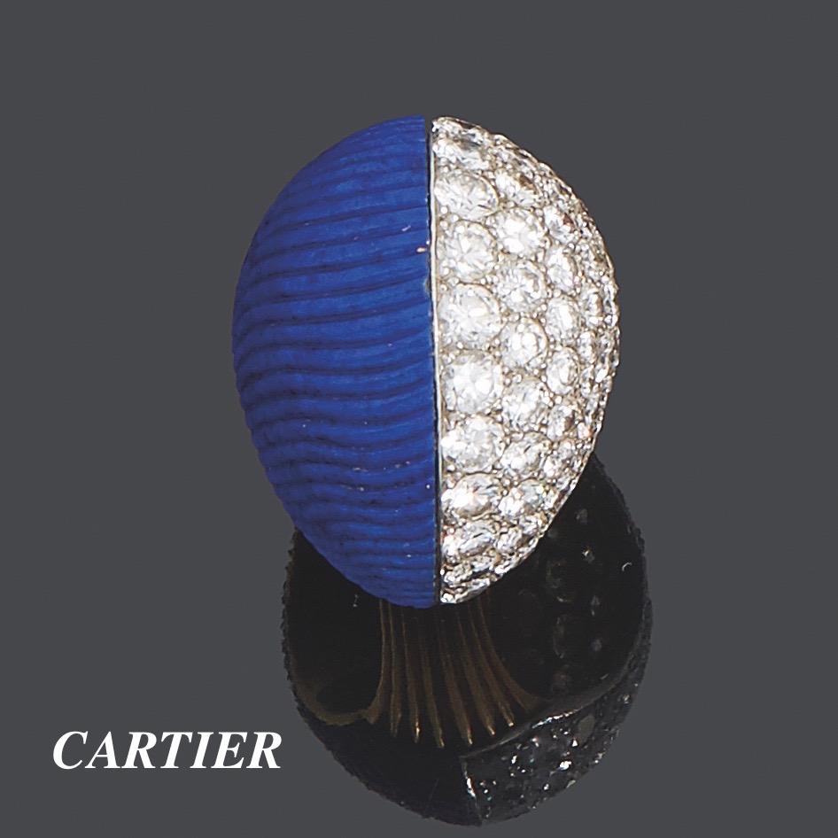 47. CARTIER Importante BAGUE modèle « Boule » en platine (950‰) et or jaune (750‰) godronné, à moitié pavée de diamants taille brillant et l'autre moitié ornée d'un lapis lazuli godronné et bombé. Travail français, vers 1969. Signée CARTIER, Paris et numérotée. Porte le poinçon de Maître du joaillier. Doigt : 53. Poids brut : 22,3 g. Bibliographie : pour le même modèle en corail, « Etourdissant CARTIER, la création depuis 1937 », Nadine COLENO, Editions du Regard, page 164 reproduit en pleine page. 2.000/4.000