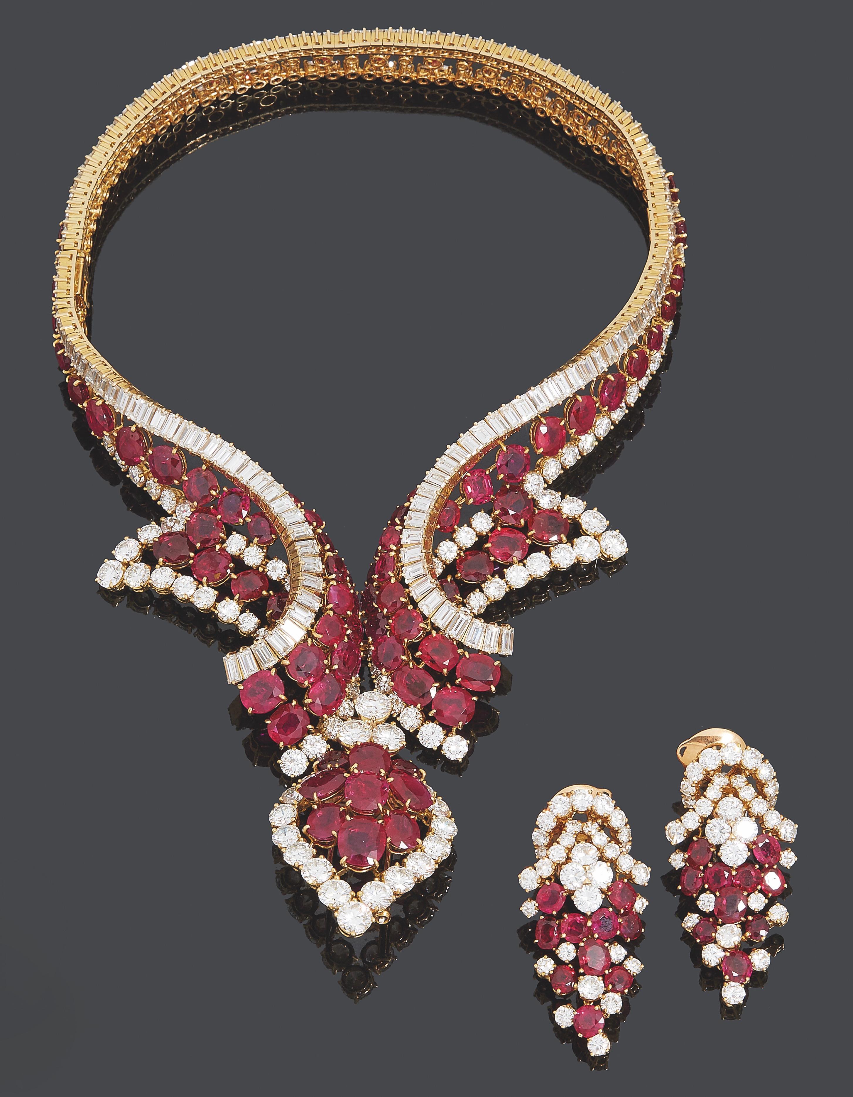 46. M. GERARD PARURE « collection MEDICIS » composée d'un COLLIER « volutes », partiellement transformable en BRACELET, d'un CLIP de CORSAGE « goutte » transformable en PENDENTIF et d'une paire de CLIPS d'OREILLES « grappe », en suite. La monture en or jaune (750‰) serti de diamants taille brillant et rubis ronds, soulignés d'alignements de diamants baguettes. Signée M. GERARD et numérotée, commande spéciale. Dans un étui M. GERARD. Expert Cukierman
