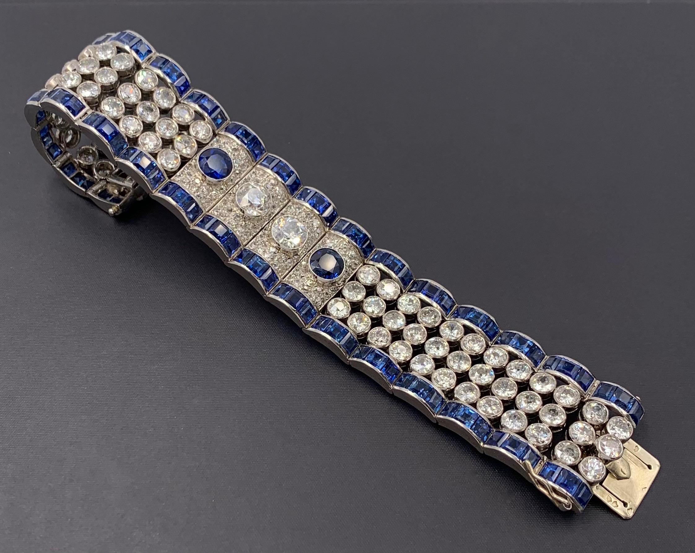 123. Important BRACELET manchette articulé en platine (950‰) et or gris (750‰) ajouré, entièrement bordé de saphirs calibrés, orné de 78 diamants taille ancienne en serti clos et composé de quatre larges godrons pavés de diamants, centrés de deux diamants taille ancienne et deux saphirs ronds. Travail français, vers 1940-50. Long. : 17,5 cm. Larg. : 2,5 cm. Poids brut : 92,4 g. Le bracelet est accompagné de dessins préparatoires originaux rehaussés de gouache, un sur papier gris (numéroté), l'autre sur papier calque (déchiré). 8.000/10.000 Expert Cukierman