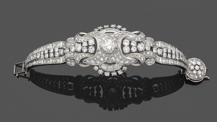 90. BRACELET semi rigide en platine (950‰) ajouré, à motifs de volutes et courbes, serti de diamants taille brillant dont un plus important au centre, et diamants taille baguette. Fermoir circulaire en suite. Travail français, vers 1935. Epoque Art Déco. Poinçon de Maître du joaillier niçois FREDIANI. Long. : 14 cm (court). Poids brut : 38,2 g. 2.500/3.000 Expert Cukierman