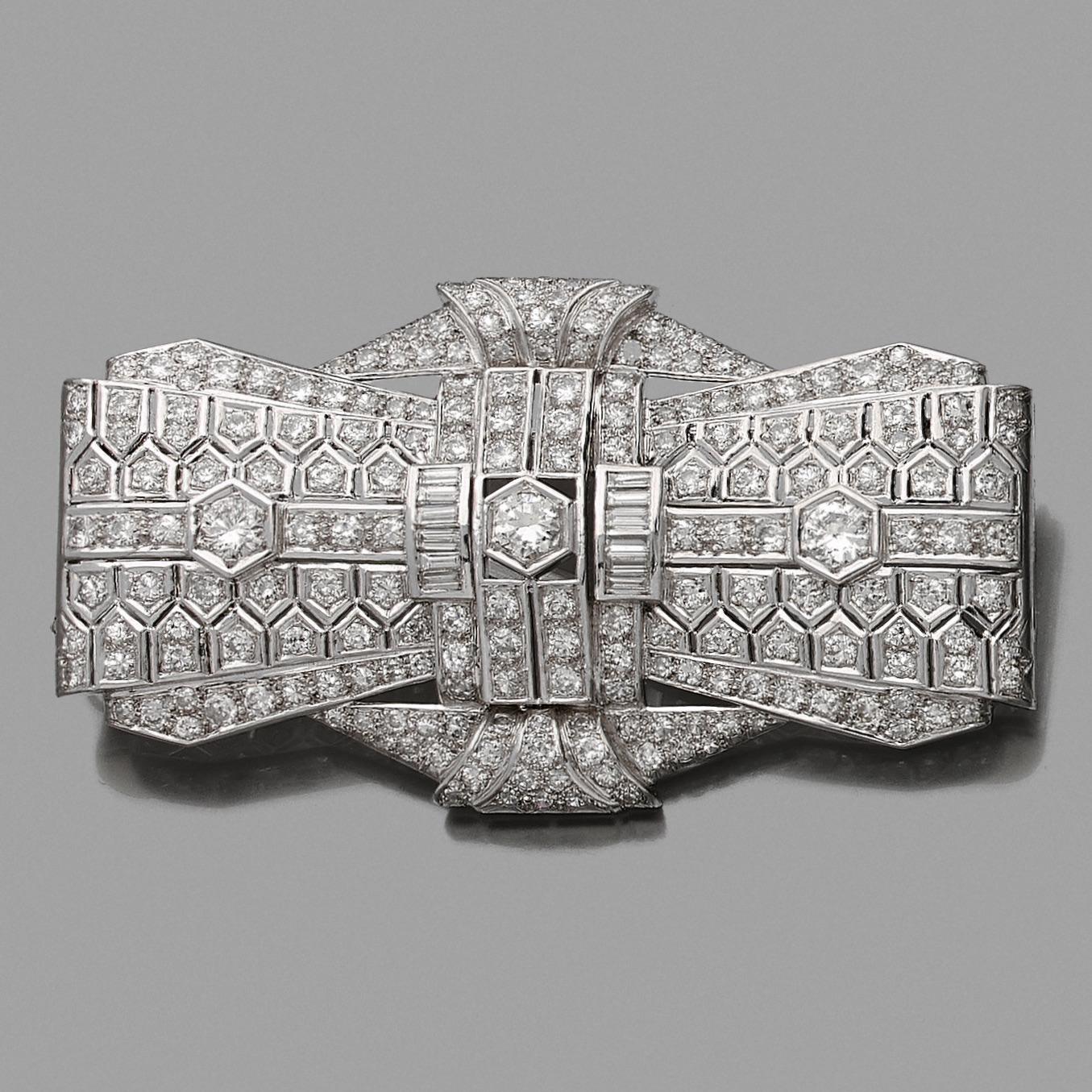 Importante BROCHE « nœud » en platine (950‰) et or gris (750‰) serti de diamants taille brillant, taille ancienne et baguette. Travail français, vers 1930. Époque Art Déco. Dans son écrin. Dim. : 7,8 x 4,4 cm. Poids brut : 40 g. 2.000/3.000 Expert Cukierman